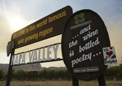 Smoke from the Nuns fire wafts over the Welcome to the Napa Valley sign, Monday, Oct. 16, 2017, in Oakville, Calif. State and local officials say they are trying to get people back into their homes, but they cautioned that it could take days and even weeks for neighborhoods hard hit by Northern California wildfires. (AP Photo/Eric Risberg)